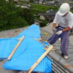 屋根の破損箇所にブルーシートをかける